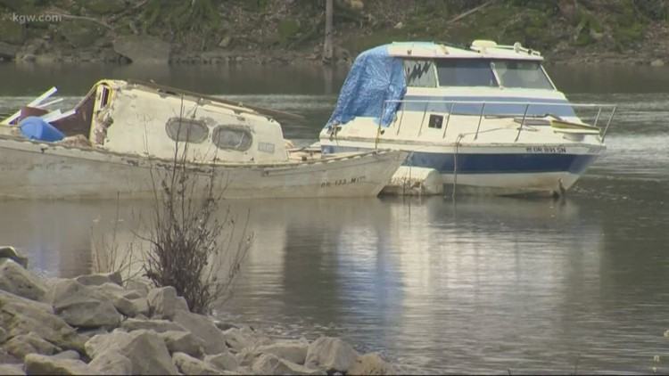 Sunken, toxic boats hauled out of river