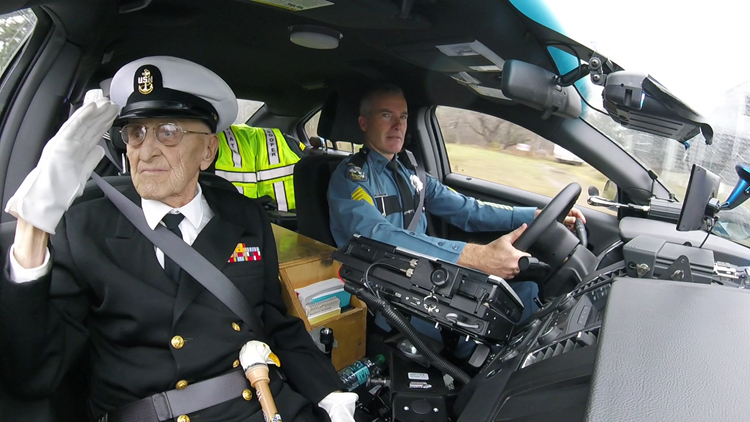 During the motorcade, Mr. Coles salutes to onlookers from the passenger seat of a Maine State Police vehicle.