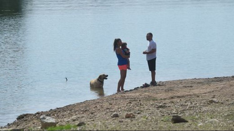 Lonnie Crim talks to his wife Pamela as she holds a toddler Lonnie pulled from a sinking SUV at Pigeon Creek Park.
