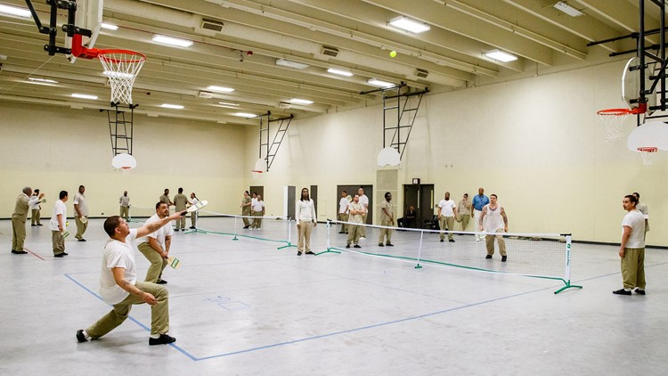 Inmates play pickleball at the Cook County Jail. Pickleball combines elements of badminton, tennis, and table tennis.